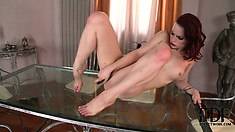 Long-haired brunette is totally naked and poses on a glass table